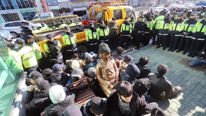 "In this Dec. 28, 2016, photo, members of civic groups sit around a comfort-woman statue after they set up in front of the Japanese consulate as police officers surround them in Busan, South Korea. Japan is recalling its ambassador to South Korea Friday, Jan. 6, 2017 in response to the placing of the statue. Many Koreans and other women in Asia were forced to work in brothels for the Japanese military during World War II in what was called the ""comfort-woman"" system. (Kim Sun-ho/Yonhap via AP)"