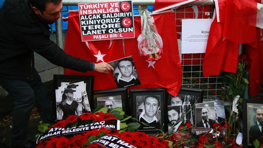A man adjusts a victim's photograph displayed with floral tributes and Turkish flags, outside the Reina night club following the New Year's day attack, in Istanbul, Wednesday, Jan. 4, 2017. Turkey has identified the gunman in the Istanbul nightclub massacre, the foreign minister said Wednesday as the president vowed that the country won't surrender to terrorists or become divided. (AP Photo/Emrah Gurel)