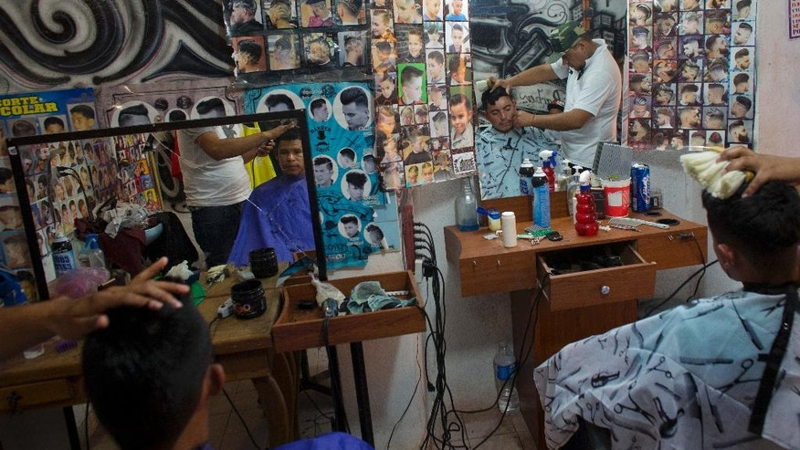 Alfredo Martinez, left, a 22-year-old robot technician at General Motors, and Angel Rodriguez, 19, who had hoped to find work at the now-cancelled Ford plant, get their hair cut at the barbershop of Omar Rojas, right, in Villa de Reyes, outside San Luis Potosi, Mexico, Wednesday, Jan. 4, 2017. Rojas and fellow barber Juan Manuel said many young people in the area, particularly from the farming communities, had been hoping to find work at Ford. (AP Photo/Rebecca Blackwell)