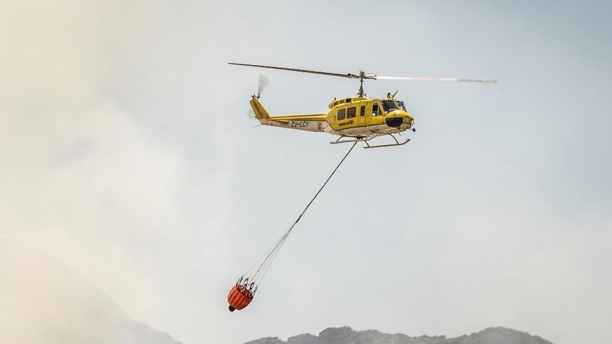 In this photo taken Wednesday, Jan. 4, 2017 a helicopter drops water over wildfires burning in the mountains in Somerset West near Cape Town, South Africa. Authorities say wildfires raging in South Africa's wine region have destroyed part of one of the country's oldest estates, while some slopes of Cape Town's Table Mountain burned. (AP Photo/Stefan Smuts)