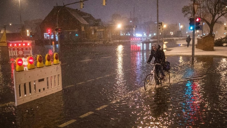 In this Thursday, Jan. 4, 2017 photo a woman rides her bicycle through flooding in Wismar, northern Germany, after the northern German coast region was hit by high tide. (Jens Buettner/dpa via AP)