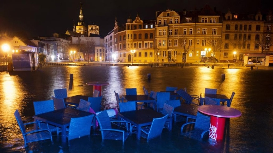 Furniture of a restaurant are surrounded by flood water in the harbor of Stralsund, northern Germany, Thursday morning, Jan. 5, 2017 after the northern German coast region was hit by high tide. (Stefan Sauer/dpa via AP)