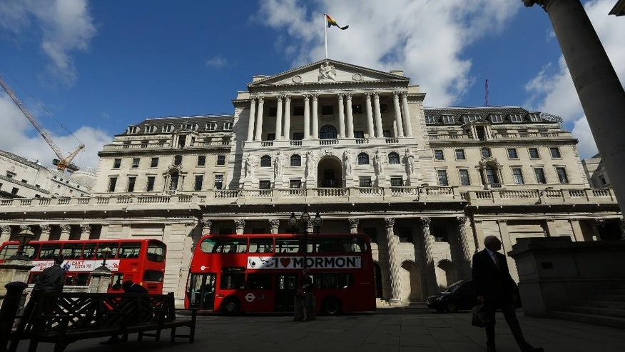 FILE - In this Friday, June, 24, 2016 file photo, Buses pass the Bank of England, in the City of London. Britain's leading stock index has struck a record high as a closely monitored survey showed manufacturers in the country expanding at their highest tick in 30 months. By late-morning Tuesday, Jan. 3, 2017 the FTSE 100 index was up 0.3 percent at 7,165. Earlier in the session, it had breached the 7,200 mark for the first time ever, trading as high as 7,205.21. (AP Photo/Matt Dunham, File)