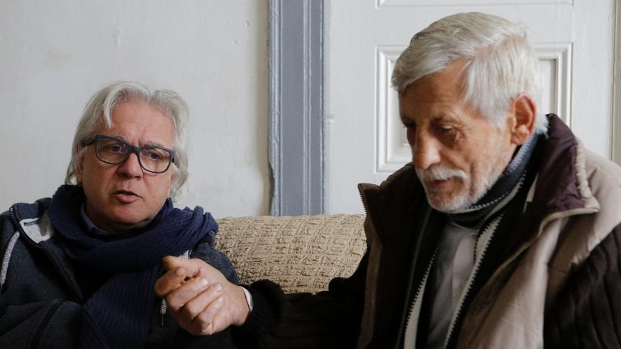 In this Wednesday, Dec. 21, 2016 photo, Greek Cypriot Michalis Georgiades, left, and Turkish Cypriot Cumar Kamir sit and talk in the house in town of Morphou in the Turkish Cypriot breakaway northern part of the divided Mediterranean island of Cyprus. Greek Cypriot Michalis Georgiades fled the home he grew up in just before Turkish troops seized the town of Morphou 42 years ago. Turkish Cypriot Cumar Kamir, himself displaced, has been living in that same house for almost as long. Georgiades says he wants his home back; Kamir says he'd gladly leave, as long as another home is built for him in his home town from which he also fled. A summit in Geneva on Jan. 2017 aiming at a deal reunifying ethnically split Cyprus could decide who gets what back. (AP Photo/Petros Karadjias)