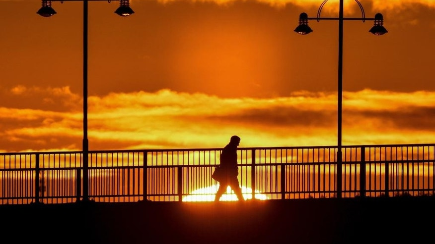 A man is silhouetted against the rising sun in Frankfurt (Oder), eastern Germany, Friday morning, Jan. 6, 2017 when temperatures dropped far under the freezing point. (Patrick Pleul/dpa via AP)