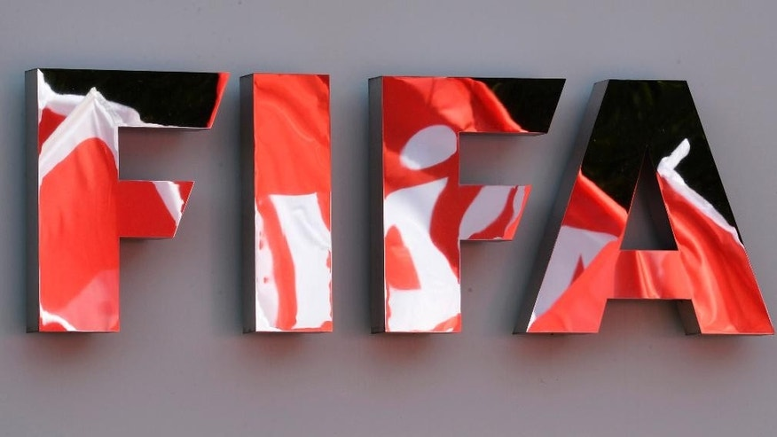 FILE - In this file photo dated Thursday, Oct. 3, 2013, Flags of the union UNIA are reflected in the FIFA logo during a demonstration in front of the FIFA headquarters against the working conditions for the soccer World Cup 2022 in Qatar.  FIFA has defeated a legal challenge by trade union groups on Friday Jan 6, 2017, at a Zurich Commercial Court over picking Qatar as 2022 World Cup host and failing to ensure reforms to labor laws. (AP Photo/Keystone, FILE, Steffen Schmidt)