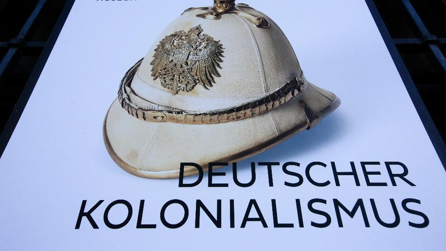 "A poster for the exhibition 'German Colonialism' with a historic German spiked helmet displayed outside the German Historic Museum in Berlin, Friday, Jan. 6, 2017. Germany says  Friday Jan. 6, 2017 it could make further payments to Namibia for the killing of 65,000 tribes people by German colonial troops during the early 20th century. Foreign Ministry spokesman Martin Schaefer says the two-year talks with Namibia's government ""aren't easy because it's a difficult topic.""  His comments come a day after representatives of the Herero and Nama tribes filed a class action complaint against the German government in the United States, seeking reparations and a place at the negotiating table. (AP Photo/Markus Schreiber)"