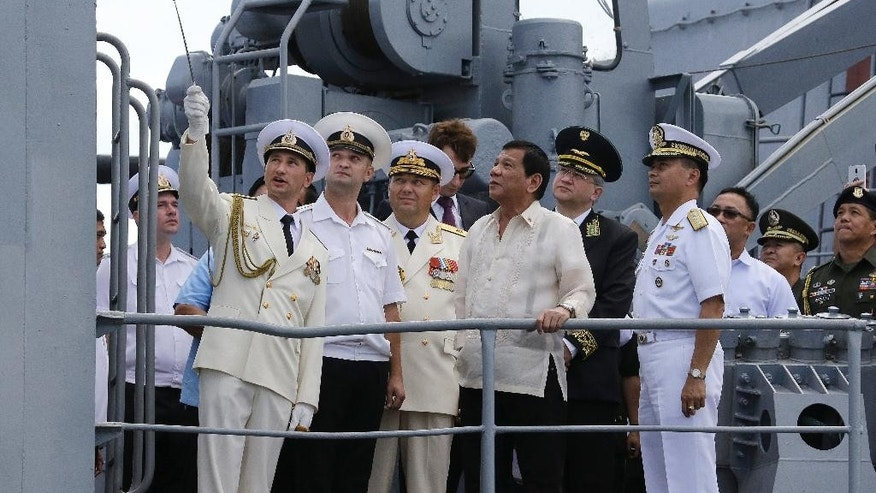 PhilippineS President Rodrigo Duterte, center, watches as Russian navy officers show the weapons on board the Russian anti-submarine Navy vessel Admiral Tributs in Manila.