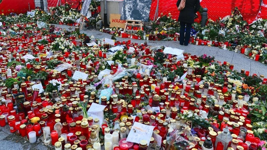 A woman attends a minute of silence between flowers and candles in memory of the victims of  the Berlin terror attack in Berlin, Thursday Jan. 5, 2017.  A police official says that German authorities knew of 14 different identities used by Berlin Christmas market attacker Anis Amri. Investigators say the 24-year-old Tunisian drove a truck into the market on Dec. 19, killing 12 people. He was killed Dec. 23 in a shootout with Italian police in a Milan suburb. (Maurizio Gambarini/dpa via AP)