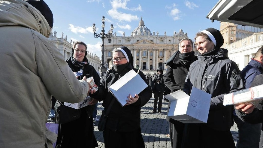 Nuns distribute food and drinks to needy people in St. Peter's square at the Vatican, Friday, Jan. 6, 2017. After the Angelus prayer Pope Francis offered some 300 needy people a simple lunch of a sandwich and drink, as part of his long-running outreach to the poor and homeless who live around the Vatican.(AP Photo/Andrew Medichini)