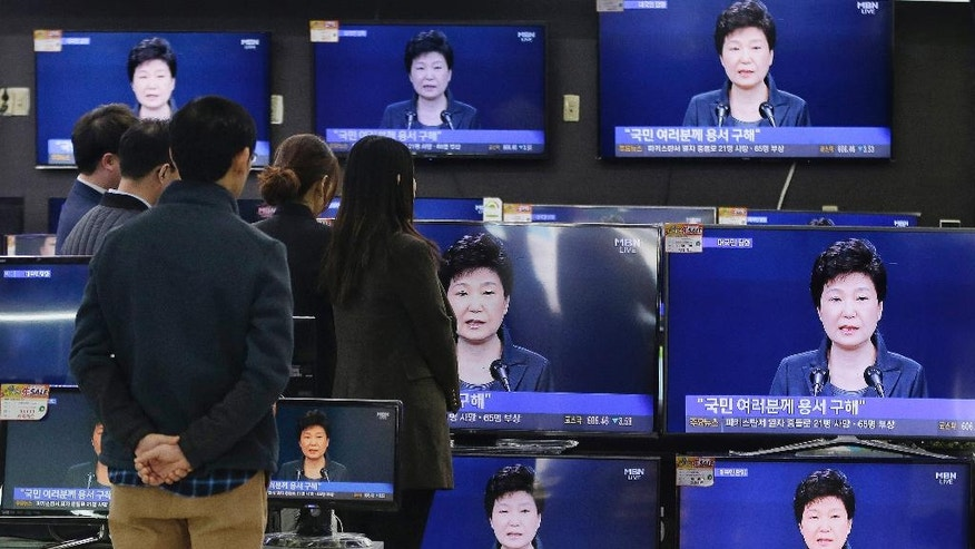 "FILE - In the Nov. 4, 2016 file photo, people watch TV screens show the live broadcast of South Korean President Park Geun-hye's address to the nation at the Yongsan Electronic store in Seoul, South Korea. A lawyer for South Korea's disgraced president has compared her impeachment to the ""unjust"" deaths of Jesus Christ and the ancient Greek thinker Socrates. That might be over the top, but the country's second impeachment trial will have major implications on the world's 11th largest economy and its tense standoff with nuclear-armed North Korea. (AP Photo/Ahn Young-joon, File)"