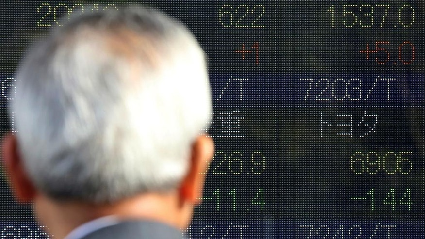"A man looks at an electronic stock board of a securities firm showing Toyota's, right, in Tokyo, Friday, Jan. 6, 2017. Toyota Motor Corp. stock fell 2 percent in early Friday morning trading after U.S. President-elect Donald Trump said on Twitter that the Japanese automaker faces a ""big border tax"" if it goes ahead with plans on a new Mexico plant. (AP Photo/Koji Sasahara)"