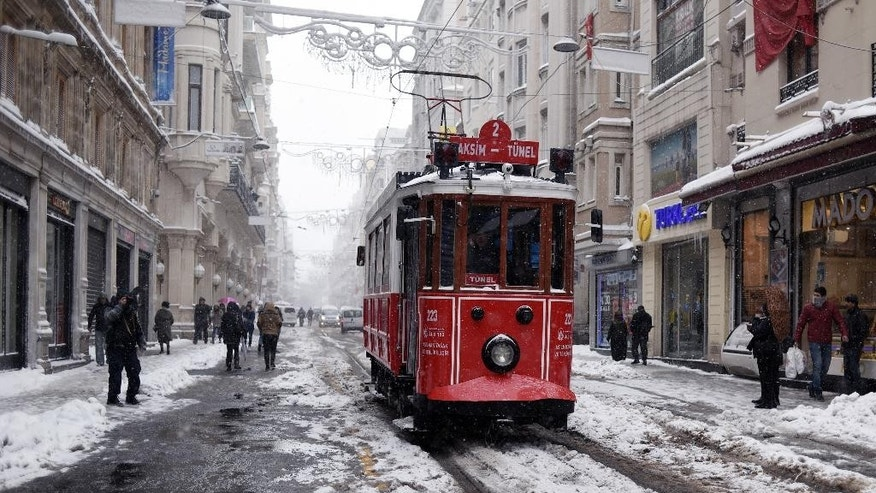 A tram is driven in central Istanbul's Istiklal Avenue, the main shopping road of Istanbul, during snowfall, Saturday, Jan. 7, 2017. Heavy snow clogged roads, shipping traffic in Bosphorus and forced hundreds of flight cancellations in the Turkish metropolis. (Mert Akyol/Depo Photos via AP)