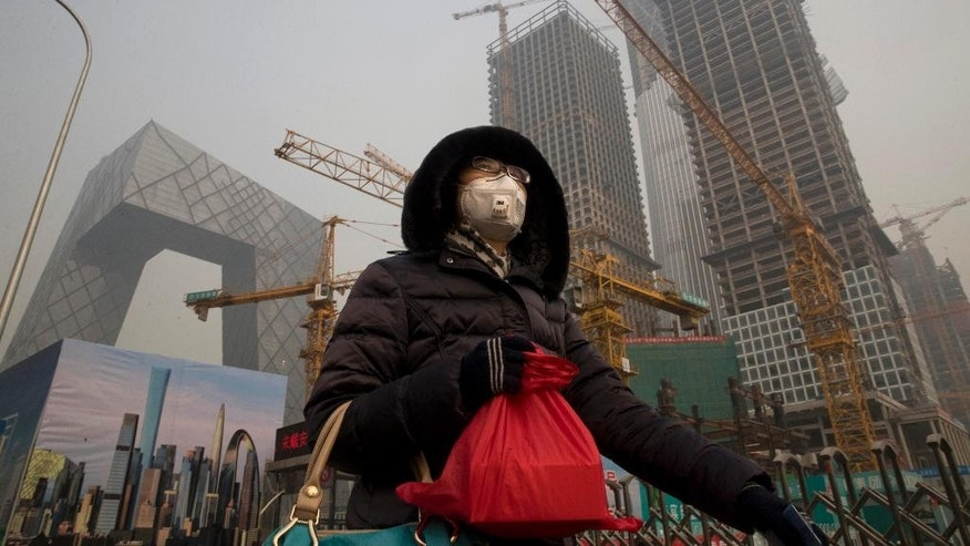 A woman wears a mask as she walks past a construction site as smog continues to choke Beijing on Friday, Jan. 6, 2017. The official Xinhua News Agency reported this week that the environmental ministry had given out punishments after finding that more than 500 construction sites and enterprises, including metallurgy, agricultural chemical and steel plants, and 10,000 vehicles had breached pollution response plans. (AP Photo/Ng Han Guan)