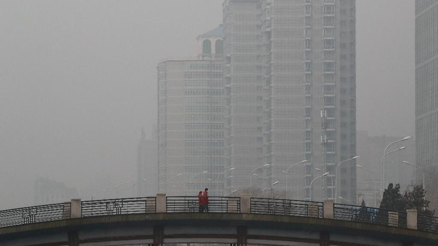 Chinese men wearing masks to filter the pollution walk on a bridge near building shrouded by fog and pollution in Beijing, Thursday, Jan. 5, 2017. China has long faced some of the worst air pollution in the world, blamed on its reliance of coal for energy and factory production, as well as a surplus of older, less efficient cars on its roads. Inadequate controls on industry and lax enforcement of standards have worsened the pollution problem. (AP Photo/Andy Wong)