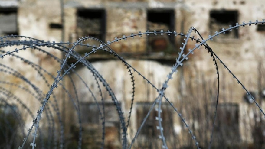 In this Wednesday, Jan. 4, 2017 photo, barbed wires in front of an abandoned building at the UN buffer zone, Green Line, that divided the Greek, south, and Turkish, north, Cypriots controlled areas in the divided capital Nicosia in the eastern Mediterranean island of Cyprus. After 19 months of talks aimed at reunifying the internationally recognized Greek Cypriot south with the breakaway Turkish Cypriot north, the final peace deal details are set to be thrashed out, potentially bringing some good news to a region wracked by conflict and distrust. (AP Photo/Petros Karadjias)