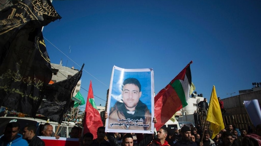 Palestinians hold up a poster of a missing fisherman, Mohammed Al-Hissi, 33, as they attend his symbolic funeral in Gaza City, Saturday, Jan. 7, 2017. The family of a Palestinian fisherman who disappeared after boat collision with an Israeli navy vessel off Gaza coast declared him dead Saturday after three days of search, accusing the Israeli military of deliberately sinking the fishing boat. (AP Photo/Khalil Hamra)