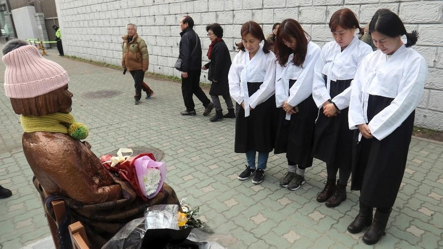 "South Korean women wearing traditional dress pay theirs respects to a ""comfort-woman"" statue set up in front of the Japanese consulate in Busan, South Korea, Friday, Jan. 6, 2017. Japan announced Friday that it would recall its ambassador to South Korea and suspend economic talks in response to the placing of a ""comfort-woman"" statue representing wartime sex slaves in front of its consulate in the Korean port city of Busan. (Kim Sun-ho/Yonhap via AP)"