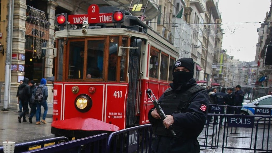 In this Thursday, Jan. 5, 2017 photo, a  tram is driven past as a Turkish police officer secures central Istanbul's Istiklal Avenue, the main shopping road of Istanbul. Turkey's economy is suffering in the face of a string of extremist attacks _ including the nightclub massacre of New Year's revelers, most of them foreigners _ and uncertainty following the failed coup in July against President Recep Tayyip Erdogan that saw more than 270 people killed. (AP Photo/ Emrah Gurel)