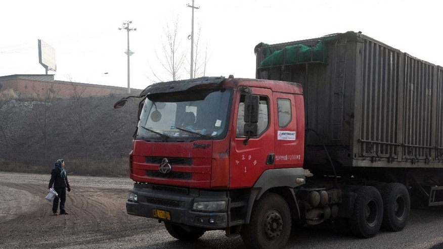 In this Dec. 30, 2016 photo, a villager surnamed Shen waits to pick up coal that fell from overfilled coal trucks tumbling down an uneven junction near the Shougang steel factory in Qianan in northern China's Hebei province. Across vast swathes of northern China, particularly in the poor countryside, residents still go to great lengths to acquire and burn coal for warmth despite government efforts to ban the practice and introduce cleaner - but costlier - types of coal or electrical heating. (AP Photo/Ng Han Guan)