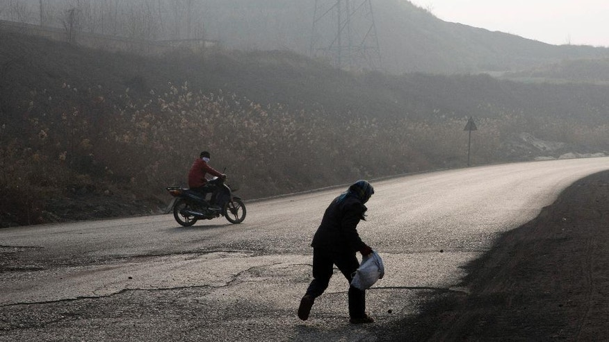 In this Dec. 30, 2016 photo, a villager surnamed Shen runs to pick up coal that fell from overfilled coal trucks tumbling down an uneven junction near the Shougang steel factory in Qianan in northern China's Hebei province. Across vast swathes of northern China, particularly in the poor countryside, residents still go to great lengths to acquire and burn coal for warmth despite government efforts to ban the practice and introduce cleaner - but costlier - types of coal or electrical heating. (AP Photo/Ng Han Guan)