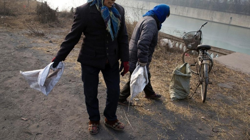 In this Dec. 30, 2016 photo, a villager surnamed Shen, right, and another wait to pick up coal that fell from overfilled coal trucks tumbling down an uneven junction near the Shougang steel factory in Qianan in northern China's Hebei province. Across vast swathes of northern China, particularly in the poor countryside, residents still go to great lengths to acquire and burn coal for warmth despite government efforts to ban the practice and introduce cleaner - but costlier - types of coal or electrical heating. (AP Photo/Ng Han Guan)