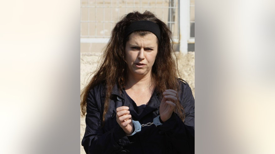 FILE - In this file photo taken Wednesday, Oct. 5, 2011, suspected terrorist Pola Roupa and alleged member of the Revolutionary Struggle group, wears handcuffs as she arrives for a trial at the maximum security Korydallos prison, western Athens. Greek police on Thursday, Jan. 5, 2017  recaptured the convicted far-left militant wanted for more than four years after she absconded during her trial on domestic terrorism charges. (AP Photo/Thanassis Stavrakis, File)