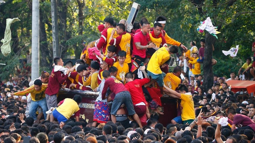 Filipino Roman Catholic devotees climb the carriage to kiss and rub with their towels the image of the Black Nazarene to celebrate its feast day Monday, Jan. 9, 2017 in Manila, Philippines. The raucous celebration drew tens of thousands of devotees in a barefoot procession for several hours around Manila streets and end up with several people injured. (AP Photo/Bullit Marquez)
