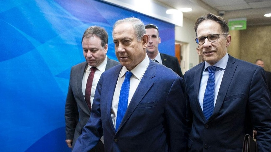 Israeli Prime Minister Benjamin Netanyahu, center, arrives to the weekly cabinet meeting at his office in Jerusalem, Sunday, Jan. 8, 2017. (Abir Sultan, Pool via AP)