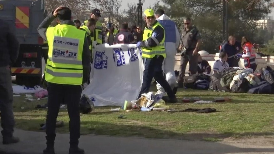This frame grab from video, shows Israeli emergency services personnel covering bodies with plastic sheets at scene of a truck-ramming attack in Jerusalem that killed at least four people and wounded several others in Jerusalem, Sunday, Jan. 8, 2017. Israeli police and rescue services said a Palestinian rammed his truck into a group of Israeli soldiers in one of the deadliest attacks of a more than yearlong campaign of violence. Security camera footage shows the truck barreling at a high speed off the road and into a crowd of people in the Armon Hanatziv neighborhood. (AP Photo)