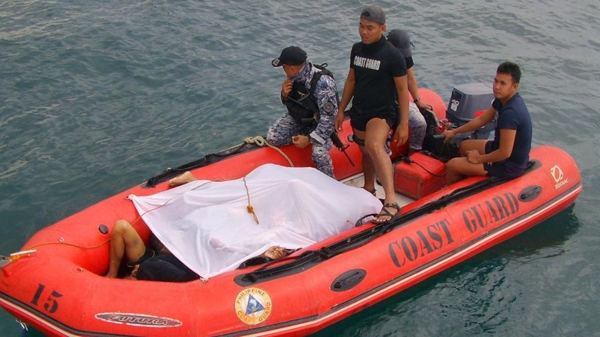 In this photo provided by the Philippine Coast Guard, members of the Philippine Coast Guard bring bodies of Filipino fishermen who were killed by suspected pirates in waters near Zamboanga City, southern Philippines Tuesday, Jan. 10, 2017. Several Filipino fishermen were killed after a group of suspected pirates boarded a fishing boat in southern Philippine waters and strafed the crew, officials said Tuesday. (Philippine Coast Guard via AP)
