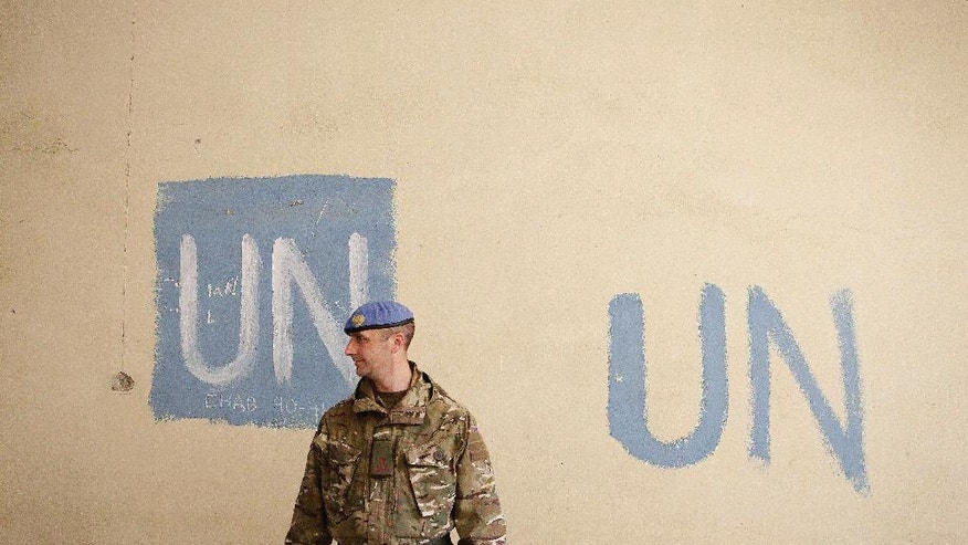 In this Wednesday, Jan. 4, 2017 photo, a UN soldier stands by an abandoned building inside the UN buffer zone, Green Line, that divided the Greek, south, and Turkish, north, Cypriots controlled areas in the divided capital Nicosia in the eastern Mediterranean island of Cyprus.  After 19 months of talks aimed at reunifying the internationally recognized Greek Cypriot south with the breakaway Turkish Cypriot north, the final peace deal details are set to be thrashed out, potentially bringing some good news to a region wracked by conflict and distrust. (AP Photo/Petros Karadjias)