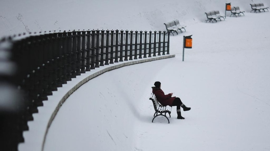 A woman sits on a bench at the government district after a heavy snowfall  in Berlin, Monday, Jan. 9, 2017. (AP Photo/Markus Schreiber)