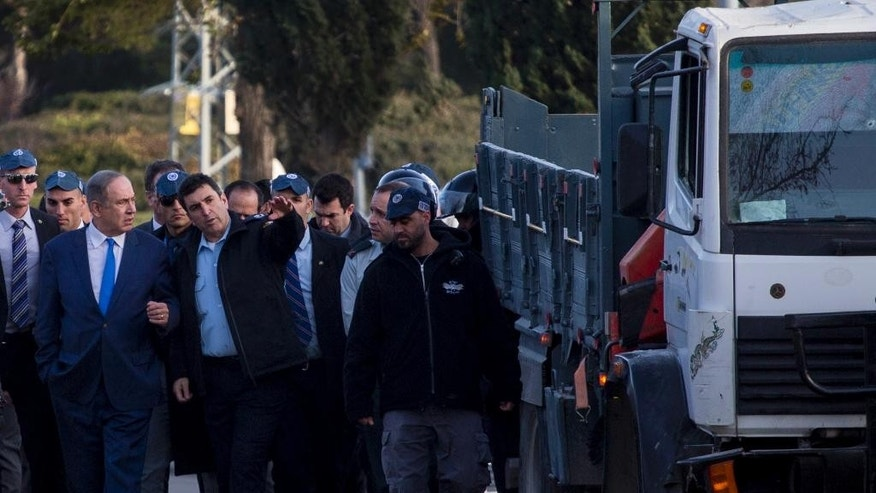 Israeli Prime Minister Benjamin Netanyahu, third left, visits the scene of an attack in Jerusalem, Sunday, Jan. 8, 2017. A Palestinian rammed his truck into a group of Israeli soldiers in Jerusalem, killing four soldiers and wounding 15 others in one of the deadliest attacks of a more than yearlong campaign of violence. Prime Minister Benjamin Netanyahu says the driver was a supporter of the Islamic State group, and suggested the attack was inspired by similar assaults in Europe, without providing any evidence. (AP Photo/Olivier Fitoussi)
