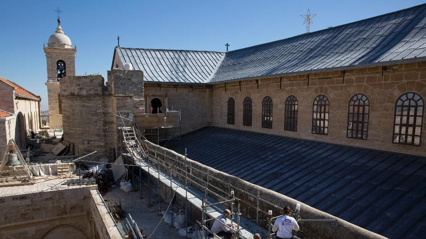 FILE - In this Feb. 4, 2016 file photo, restoration experts work on the the rooftop of the Church of the Nativity, in the West Bank city of Bethlehem. The Italian firm restoring one of Christianity's holiest sites _ the Church of the Nativity in Bethlehem _ says Monday Jan. 9, 2017, it's more than halfway finished with the 14 million-euro project, which has already uncovered a Crusades-era mosaic angel hidden under plaster. (AP Photo/Nasser Nasser, File)