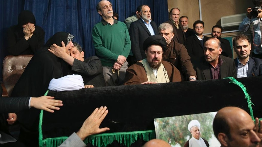 CAPTION CORRECTS THE LOCATION OF THE CHILDREN - Hassan Khomeini, center, grandson of Iran's late revolutionary founder Ayatollah Khomeini, mourns over the coffin of former President Akbar Hashemi Rafsanjani, as Rafsanjani's son Mahdi, second left, comforts his sister Fatemeh, at the Jamaran mosque in northern Tehran, Iran, Sunday, Jan. 8, 2017. Rafsanjani died Sunday after a decades-long career in the ruling elite, where his moderate views were not always welcome but his cunning guided him through revolution, war and the country's turbulent politics. (AP Photo/Vahid Salemi)