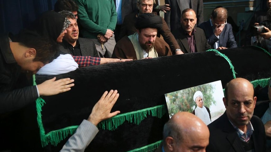 Hassan Khomeini, center, grandson of Iran's late revolutionary founder Ayatollah Khomeini, mourns over the coffin of former President Akbar Hashemi Rafsanjani at the Jamaran mosque in northern Tehran, Iran, Sunday, Jan. 8, 2017. Rafsanjani died Sunday after a decades-long career in the ruling elite, where his moderate views were not always welcome but his cunning guided him through revolution, war and the country's turbulent politics. (AP Photo/Vahid Salemi)