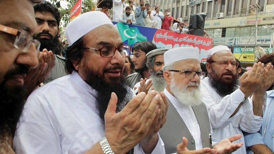 FILE -- In this July 19, 2016 file photo, Hafiz Saeed, third left, the leader of Pakistan's anti-Indian group Lashkar-e-Taiba, that was banned but resurrected as the Jamaat-ud-Daawa, prays for Indian Kashmiris with others during an anti-Indian rally in Lahore, Pakistan. Two Pakistani research groups have noted a significant drop in militant violence in the country last year but say that for the trend to continue, authorities need to fight sectarian and anti-Indian extremists based in the most populous Punjab province. (AP Photo/K.M. Chaudary, File)