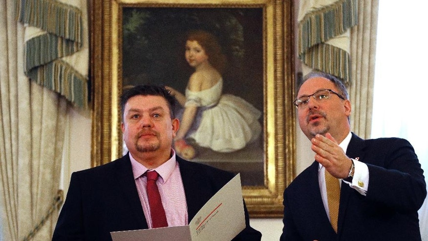 Polish Ambassador Arkady Rzegocki, right, welcomes British lorry driver David Duncan at the Polish Embassy in London, Monday, Jan. 9, 2017. The British lorry driver from West Yorkshire led a fundraising campaign in support of the family of the late Lukasz Urban, a fellow trucker killed in the Berlin attack in December last year. (AP Photo/Frank Augstein)