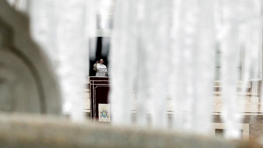 Pope Francis, framed by icicles hanging from a frozen fountain, delivers his blessing during the Angelus noon prayer he celebrated from the window of his studio overlooking St. Peter's Square, at the Vatican, Sunday, Jan. 8, 2017. (AP Photo/Andrew Medichini)