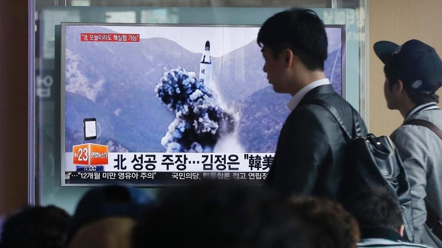 FILE - In this April 24, 2016 file photo, a man walks by as people watch a TV news program showing an image published earlier in the day in North Korea's Rodong Sinmun newspaper of North Korea's ballistic missile that the North claimed to have launched from underwater, at Seoul Railway station in Seoul, South Korea. With Donald Trump getting ready to become president, North Korea is talking about launching an ICBM and Washington officials are saying they will shoot down anything that threatens the territory of the U.S. or its allies. (AP Photo/Ahn Young-joon, File)