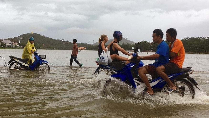 FILE - In this Jan. 5, 2017, file photo, riders use a road flooded by an overflowing lake on Ko Samui, Thailand. Authorities say at least 25 people have died in severe flooding in southern Thailand since New Year's, leaving businesses paralyzed and thousands of tourists stranded. The Interior Ministry said in a report Tuesday that the main highway connecting the south with the rest of the country was swamped. (AP Photo/Adam Schreck, File)