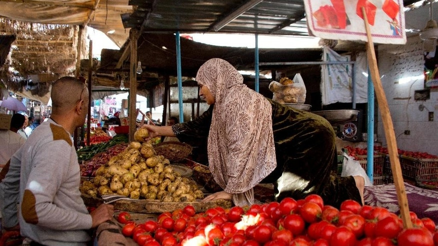 FILE -- In this Nov. 25, 2016 file photo, a vegetable vendor sells produce at a market in Cairo, Egypt. Egypt is seeing a dramatic jump in the country's annual urban consumer price inflation. In a  Tuesday, Jan. 10, 2017, statement, the state-run Central Agency for Public Mobilization and Statistics said that inflation has reached a record high of 24.3 percent, the highest in six years. The agency said food and beverage prices increased around 5.2 percent in December, and that medical care jumped to nearly 5.6 percent, compared to November. (AP Photo/Amr Nabil, File)
