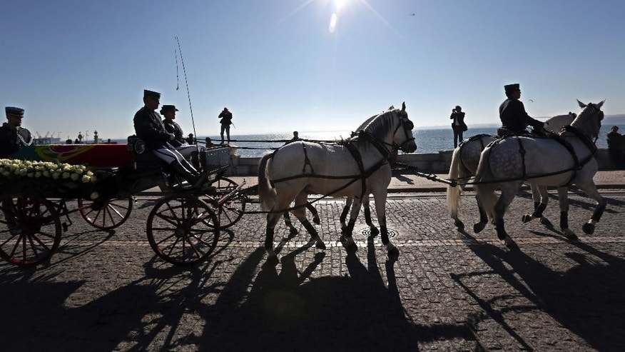 The casket of former prime minister and president of Portugal Mario Soares is carried on a horse-drawn carriage during a funeral procession along the Tagus river bank in Lisbon, Monday, Jan. 9 2017. Soares, who helped steer his country toward democracy after a 1974 military coup, died Saturday aged 92. A state funeral will be held Tuesday. (AP Photo/Armando Franca)