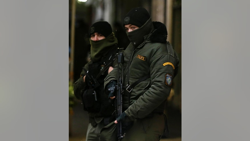 Policemen guard outside the Pan-Hellenic Socialist Movement (PASOK) offices after a gunman opened fire at a police bus in Athens, on Tuesday, Jan. 10, 2017. Authorities say a police officer has been wounded after shots were fired outside the offices of the political party in an area of Athens where anarchist groups frequently clash with police and attack symbols of authority. (AP Photo/Thanassis Stavrakis)