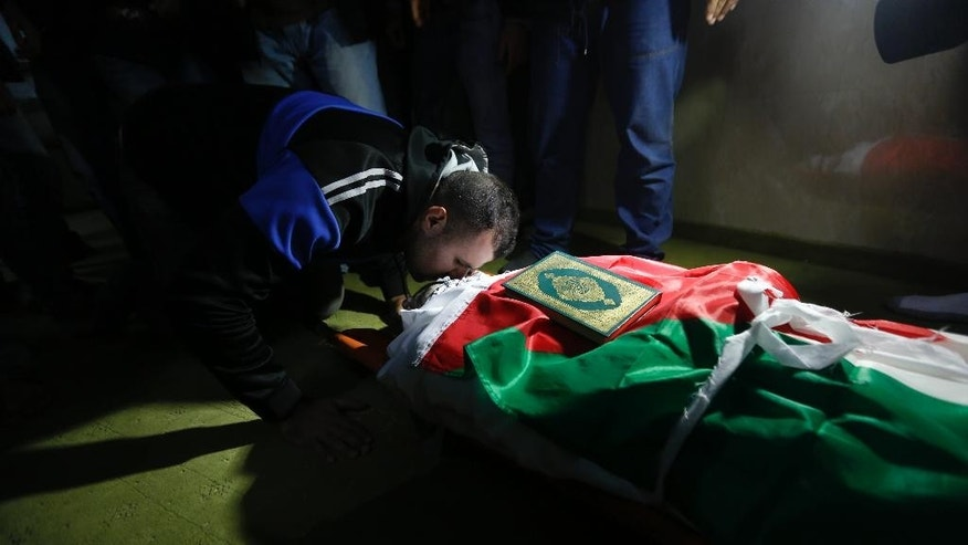 Palestinian kisses 32-year-old Mohammed al-Salhi during his funeral  in Fara Refugee Camp near the West Bank city of Nablus, Tuesday, Jan. 10 2017. Israeli military said troops have shot dead al-Salhi when he tried to stab soldiers in the West Bank. Palestinians said al-Salhi was shot dead in his home. (AP Photo/Majdi Mohammed)