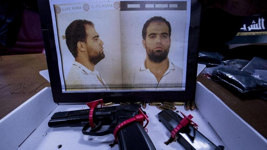 The mugshot of Hmidi Saber, who was already in jail in Rome serving another sentence, some bullets and a gun confiscated by police in his house, are shown during a press conference at the police headquarters in Rome, Tuesday, Jan. 10, 2017. Italian police issued a new arrest warrant to the Tunisian man who allegedly had links with Ansar Al Sharia and IS and was recruiting and radicalising Muslim inmates in prison. (Massimo Percossi/ANSA via AP)