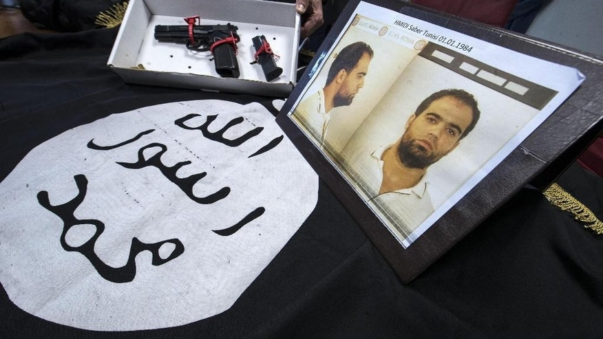 The mugshot of Hmidi Saber, who was already in jail in Rome serving another sentence, a gun and a black flag confiscated by police in his house, are shown during a press conference at the police headquarters in Rome, Tuesday, Jan. 10, 2017. Italian police issued a new arrest warrant to the Tunisian man who allegedly had links with Ansar Al Sharia and IS and was recruiting and radicalising Muslim inmates in prison. (Massimo Percossi/ANSA via AP)