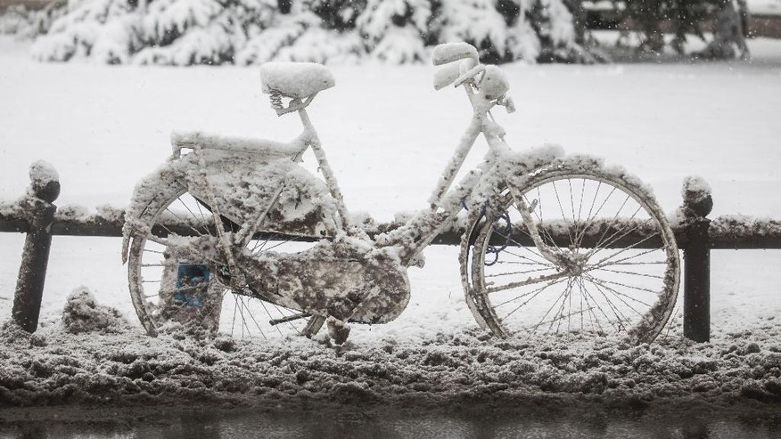 A snow-covered bicycle stands on a roadside in Wiesbaden, western Germany, Tuesday, Jan. 10, 2014. (Frank Rumpenhorst/dpa via AP)