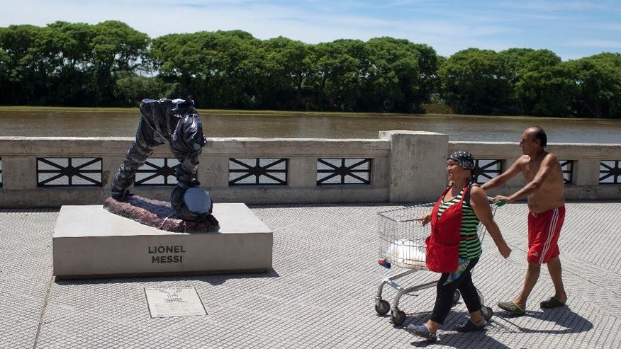 A couple walks next to the severed statue of soccer star Lionel Messi in Buenos Aires, Argentina, Tuesday, Jan. 10, 2017. The city government reported Monday night Messi's statue was destroyed and said they are already working on repairing it.(AP Photo/Natacha Pisarenko)